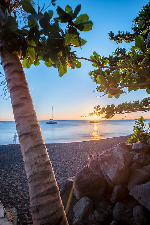 A long exposure of locals and tourists, both gathering at Black Sand Beach by Basse Terre for a view of the brilliant Caribbean sunset, as seen through Mangrove trees