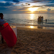 Thai boy selling sky lanterns on the beach at sunset, Phuket, Thailand
