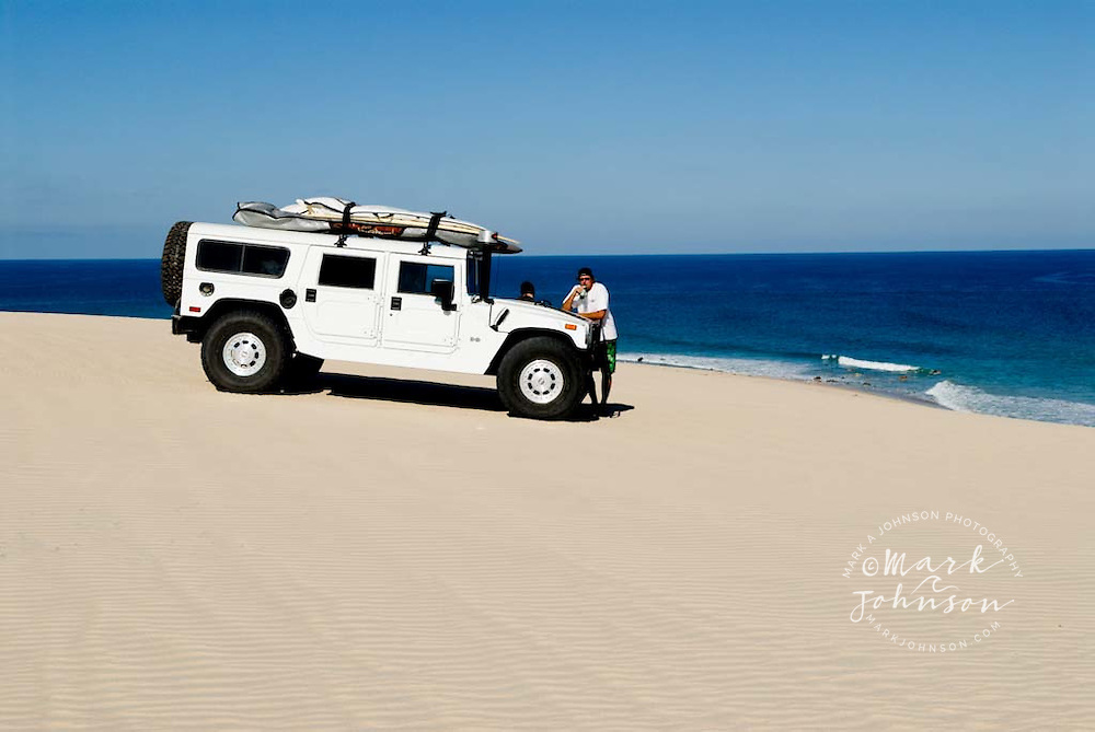 Surfers & Hummer on sand dune in Baja, Mexico