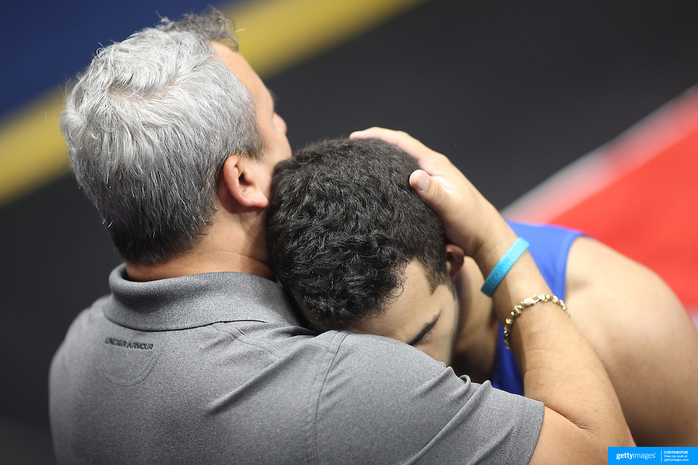 Yin Alvarez, coach and step father, embraces Danell Leyva, Homestead, Florida, after his performance on Horizontal bar during the Senior Men Competition at The 2013 P&G Gymnastics Championships, USA Gymnastics' National Championships at the XL, Centre, Hartford, Connecticut, USA. 16th August 2013. Photo Tim Clayton