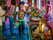 "24 JUNE 2017 - BANG KRUAI, NONTHABURI: People make on offering of flowers after a rebirthing ceremony at Wat Ta Kien (also spelled Wat Tahkian), a Buddhist temple in the suburbs of Bangkok. People go to the temple to participate in a ""Resurrection Ceremony."" Thai Buddhists believe that connecting people by strings around their heads, which are connected to a web of strings suspended from the ceiling, amplifies the power of the prayer. Groups of people meet and pray with the temple's Buddhist monks. Then they lie in coffins, the monks pull a pink sheet over them, symbolizing their ritualistic death. The sheet is then pulled back, and people sit up in the coffin, symbolizing their ritualist rebirth. The ceremony is supposed to expunge bad karma and bad luck from a person's life and also get people used to the idea of the inevitability of death. Most times, one person lays in one coffin, but there is family sized coffin that can accommodate up to six people. The temple has been doing the resurrection ceremonies for about nine years.     PHOTO BY JACK KURTZ"