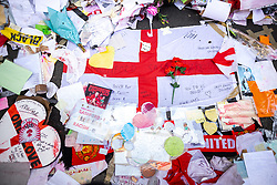 """© Licensed to London News Pictures. 23/07/2021. Manchester, UK. Volunteers and staff from the Institute for Cultural Practices at Manchester University , Manchester Art Gallery and the People's History Museum work to clean up and salvage tributes left at a memorial that grew up around a mural to England footballer Marcus Rashford , after storms and heavy rain hit the region overnight . The mural , painted by local artist """" Akse P19 """" on the side of a cafe in Withington , was defaced after England's loss to Italy on penalties in the final of the European Cup , prompting support for England's black players and anger towards the racism that had been shown towards those black players , following the match . Photo credit: Joel Goodman/LNP"""