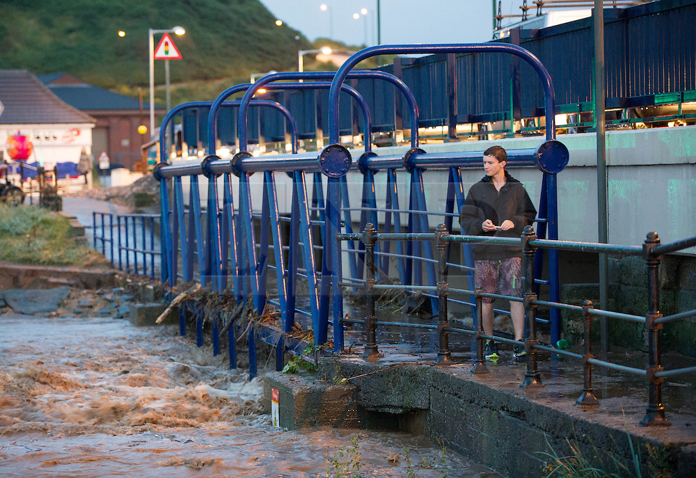 © Licensed to London News Pictures. 06/09/2013<br /> <br /> Saltburn, Cleveland, England<br /> <br /> A man walks across a bridge as heavy flooding hits in Saltburn in Cleveland.<br /> <br /> Photo credit : Ian Forsyth/LNP