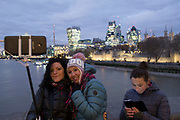 Tourists take selfies on their cellphone from Tower Bridge with the City of London financial district lit up at night behind them in London, England, United Kingdom.