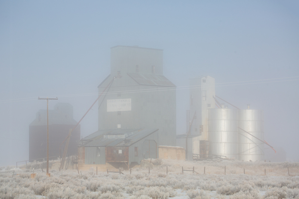 Grain Storage Elevators on the Camas Prairie at Corral Idaho awaken to early morning fog in early winter.  Morning light illuminates a complex of Agriculture Elevators on the Camas Prairie in Southwest Idaho near Fairfield.  Licensing and Open Edition Prints.