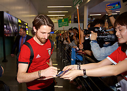 NANNING, CHINA - Monday, March 19, 2018: Wales' Joe Allen signs autographs for supporters as the team arrive at Nanning International Airport for the 2018 Gree China Cup International Football Championship. (Pic by David Rawcliffe/Propaganda)