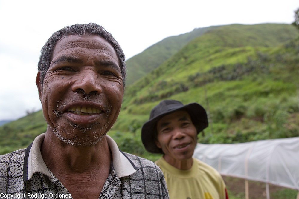 (From left to right) Farmers Sipa, who estimates his age at 60, and Nipawarti, 40, pose for a photograph by their plots of land. In October 2012 a wildfire spread quickly near their plots, threatening to set several houses on fire. Along with other community members, they used branches to hit the flames and extinguish the fire. Their land is in Sembalun Lawang, Sembalun district, East Lombok, West Nusa Tenggara province.
