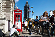 Members of the public walk past artist Marquies Hill sitting on the floor painting an iconic red telephone box situated in Parliament Square on 18th September 2019 in London, United Kingdom.