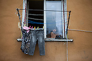 A child is watching out of a flat window in an area which is mostly populated by Roma in Moldava nad Bodvou.
