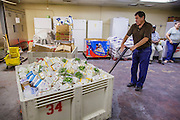 07 AUGUST 2012 - TOLLESON, AZ:   A volunteer wheels a crate of refrigerated food into position at the food bank in Tolleson, AZ, about 15 miles west of Phoenix. The Tolleson food bank has been operating for more than 20 years. It used to serve mostly the families of migrant farm workers that worked the fields around Tolleson but in the early 2000's many of the farms were sold to real estate developers. Now the food bank serves both farm worker families and people who lost their homes in the real estate crash, that his Phoenix suburbs especially hard. More than 150 families a day are helped by the Tolleson food bank, an increase of more than 50% in the last five years.    PHOTO BY JACK KURTZ
