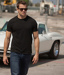good looking man in a black tee shirt and sunglasses walking by a Corvette