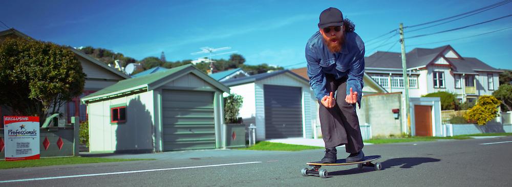 A bearded skateboarder makes a rude gesture towards the camera. Miramar, Wellington, New Zealand.
