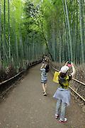 people taking pictures at the bamboo lined path Japan, Honshu, Sagano, Arashiyama