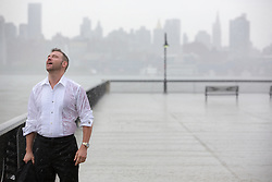 handsome middle aged man in a tuxedo shirt standing on a pier in Hoboken, NJ in the rain with his eyes closed and mouth open
