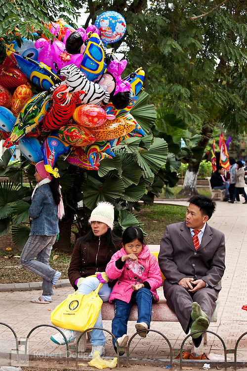 A family dressed in their best haberdashery pass the time in a Hanoi park, as is the custom during Tet, the Lunar New Year. Balloon salesmen roam the city selling the colorful ones to children. Robert Dodge, a Washington DC photographer and writer, has been working on his Vietnam 40 Years Later project since 2005. The project has taken him throughout Vietnam, including Hanoi, Ho Chi Minh City (Saigon), Nha Trang, Mue Nie, Phan Thiet, the Mekong, Sapa, Ninh Binh and the Perfume Pagoda. His images capture scenes and people from women in conical hats planting rice along the Red River in the north to men and women working in the floating markets on the Mekong River and its tributaries. Robert's project also captures the traditions of ancient Asia in the rural markets, Buddhist Monasteries and the celebrations around Tet, the Lunar New Year. Also to be found are images of the emerging modern Vietnam, such as young people eating and drinking and embracing the fashions and music of the West. His book. Vietnam 40 Years Later, was published March 2014 by Damiani Editore of Italy.