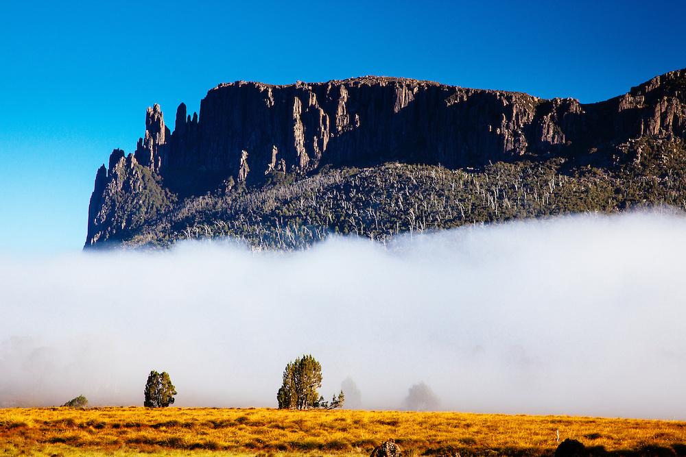 Fog rolling along the buttongrass Pelion Plains below the dolerite cliffs of Mt Oakleigh. Overland Track, Tasmania.