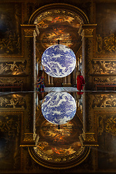 """© Licensed to London News Pictures. 01/06/2021. LONDON, UK. Staff view artist Luke Jerram's """"Gaia"""" installed in the Painted Hall at the Old Royal Naval College in Greenwich.  The scale replica of Earth rotates slowly aiming to inspire a sense of the Overview Effect that astronauts experience when they see Earth from space.  The work is on display until 1 July.  Photo credit: Stephen Chung/LNP"""