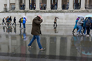 A bald pedestrian walks through rain beneath the columned architecture of the National Gallery in Trafalgar Square, Westminster, on 9th April 2019, in London, England.