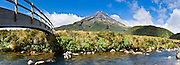 """A footbridge arches across a stream near Mount Egmont or Taranaki (2518 meters / 8261 feet) in Mount Egmont National Park, New Zealand, North Island. Featured as a stand-in for Mount Fuji in the Tom Cruise motion picture, """"The Last Samurai"""". Panorama stitched from 4 overlapping photos."""