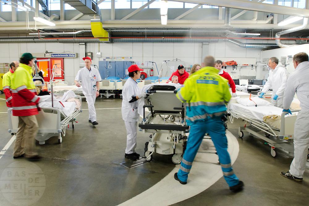 Drukte in de ambulancesluis. In het Calamiteitenhospitaal in Utrecht wordt een rampenoefening gehouden. De nadruk ligt op de contaminatie, door een gekantelde vrachtwagen zijn veel slachtoffers in aanraking gekomen met een chemische stof. Voor het eerst wordt er geoefend met een zogenaamde decontaminatietent. Als de tent bevalt, schaft het ziekenhuis zo'n tent aan. Bij de 'ramp' zijn 100 slachtoffers gevallen.<br /> <br /> Patients at the ambulance entry. In the Trauma and Emergency Hospital in Utrecht an calamity training was held. The emphasis is on the contamination by an overturned truck, many victims are contaminated by a chemical. For the first time a so-called decontamination tent was used. If the tent fulfills the expectations, a tent will be purchased. The 'calamity' caused 100 victims.