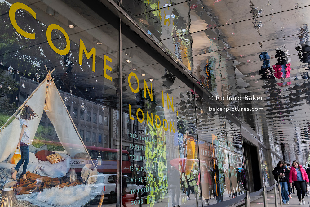 On the day that the UK government eased Covid restrictions to allow non-essential businesses such as shops, pubs, bars, gyms and hairdressers to re-open, shoppers are sen reflected in the mirrored ceiling outside John Lewis on Oxford Street, on 12th April 2021, in London, England.