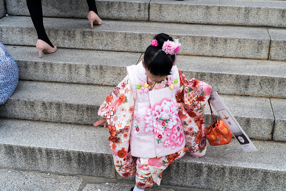 little girl celebrating her Shichi Go San coming down the stairs while an adult woman go's up