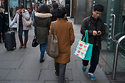 Shoppers on Oxford Street, one of whom is engrossed in texting on his mobile phone, London, England, UK.
