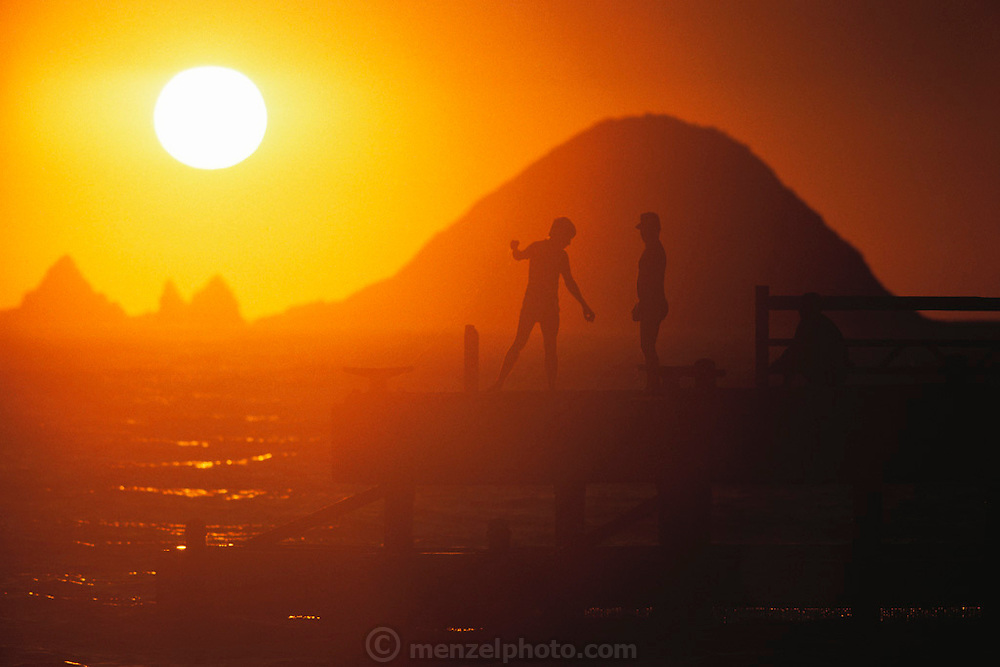 Fishing from the dock with a large setting sun behind, Ixtapa, Mexico.