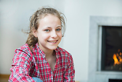 Portrait of girl sitting in front of fireplace, smiling