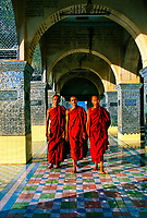 Monks walking through arches at Sutaungpyi Pagoda, on top of Mandalay Hill, Mandalay, Myanmar (Burma)