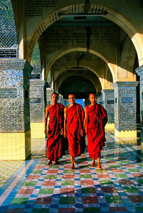 Monks walking through arches at Sutaungpyi Pagoda, on top of Mandalay Hill, Mandalay, Myanmar (Burma)