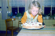 birthday blowing out the candles on a cake late 1960s