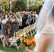 Bride Tiffany walks down the aisle at her Forest House Lodge wedding in Foresthill, California.