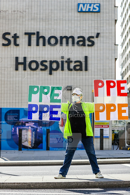 A woman holding up signs (PPE-Personal Protection Equipment) stands outside St Thomas' Hospital in central London as British Prime Minister Boris Johnson is in intensive care fighting the coronavirus in London, Tuesday, April 7, 2020. (Photo/Vudi Xhymshiti)