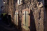 Closed wooden shutters in the late sunshine in pretty French medieval walled village of Lagrasse on the River Orbieu, on 23rd May, 2017, in Lagrasse, Languedoc-Rousillon, south of France. Lagrasse is listed as one of France's most beautiful villages and lies on the famous Route 20 wine route in the Basses-Corbieres region dating to the 13th century.