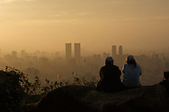A couple relaxes and watches the sunset from Elephant Mountain in Taipei, Taiwan.