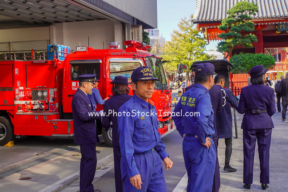Fire fighters and red fire truck in a fire station in Tokyo, Japan