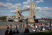 Tourists at Tower Bridge in London, England, United Kingdom. Scenes of both tourists and local office workers enjoying hanging out on the piazza at the London Bridge City Park near to Tower Bridge. This area is an icon for tourism, bringing thousands of people in each day.