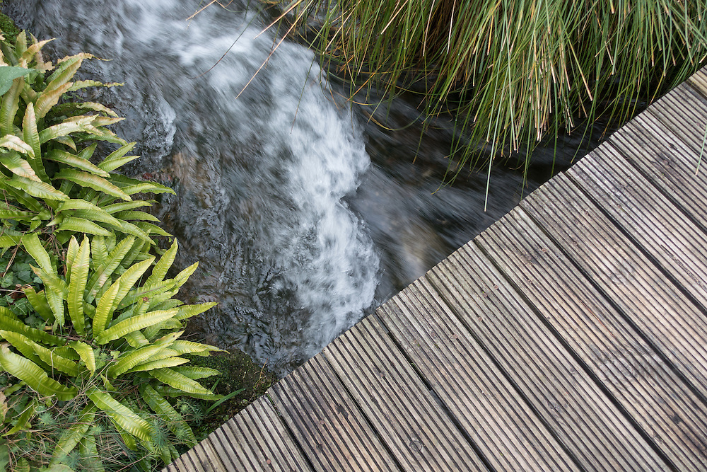 Rushing brook flows under wooden slatted walkway, green foliage lines both sides of the water.