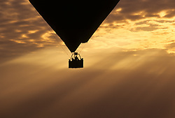 Africa, Kenya. Hot air balloon silhouetted by dramatic sunset and clouds.