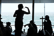 Silhouette of a female darts player concentrating on throwing arrows during a ladies darts tournament