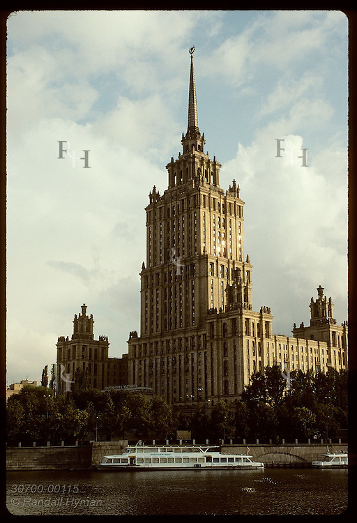 Hotel Ukraina-one of seven skyscrapers Stalin erected in the 50s, dwarfs tour boat on Moscow River Russia