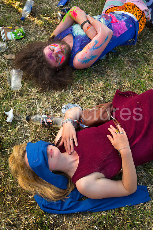 Glastonbury Festival, 2015.<br /> People sleeping on the grass in the hot afternoon sun