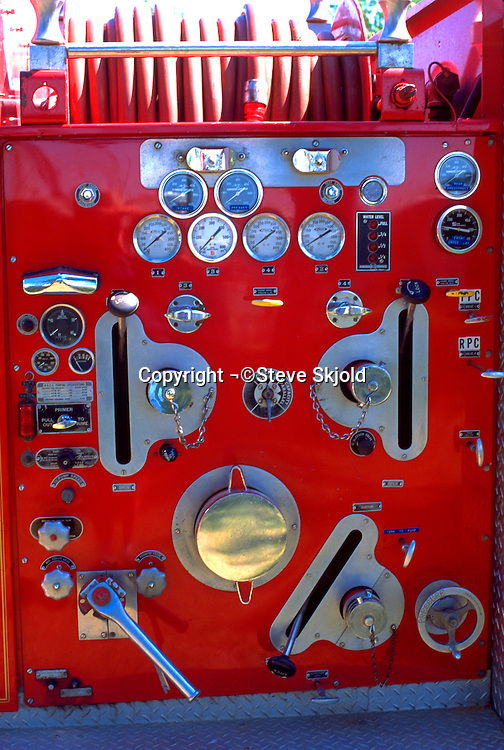 Dials knobs and hoses on the side of a fire truck at a parade.  Battle Lake Minnesota USA