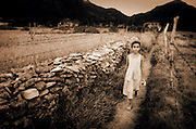 A young girl walks through a field on a path lined with stone and barbed wire.