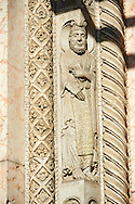 Sculptures of one of the prophets who fortold the coming of Christ and pillars of the archivolts on the main portal of the of the 12th century Romanesque Ferrara Duomo, Italy . Ferrara Cathedral (Basilica Cattedrale di San Giorgio, Duomo di Ferrara) is a Roman Catholic cathedral and minor basilica in Ferrara, Northern Italy. The original Romanesque design of Ferrara Cathedral is manifest in the façade. In the centre of the façade of Ferrara Cathedral is a porch, supported by two columns with Atlases seated on lions at the bases. It is decorated with a Last Judgement by an unknown master and a loggia with a Madonna and Child (a late Gothic addition). The portal of Ferrara Cathedral is the work of the sculptor Nicholaus, a pupil of Wiligelmus. The lunette shows Saint George, patron saint of Ferrara, slaying the dragon; scenes from the Life of Christ appear on the lintel. The jambs framing the entrance of Ferrara Cathedral are embellished with figures depicting the Annunciation and the four prophets who foretold the coming of Christ.<br /> <br /> Visit our ITALY PHOTO COLLECTION for more   photos of Italy to download or buy as prints https://funkystock.photoshelter.com/gallery-collection/2b-Pictures-Images-of-Italy-Photos-of-Italian-Historic-Landmark-Sites/C0000qxA2zGFjd_k<br /> <br /> If you prefer to buy from our ALAMY PHOTO LIBRARY  Collection visit : https://www.alamy.com/portfolio/paul-williams-funkystock/ferrara.html .