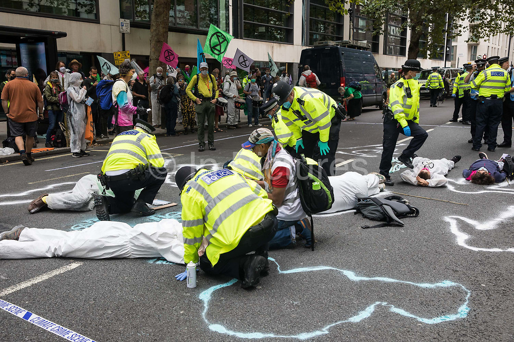 Metropolitan Police officers issue warnings to climate activists from Extinction Rebellion wearing hazmat suits who had occupied the street outside the Department of Transport in protest against roadbuilding on 3 September 2020 in London, United Kingdom. Extinction Rebellion activists are attending a series of September Rebellion protests around the UK to call on politicians to back the Climate and Ecological Emergency Bill CEE Bill which requires, among other measures, a serious plan to deal with the UK's share of emissions and to halt critical rises in global temperatures and for ordinary people to be involved in future environmental planning by means of a Citizens' Assembly.