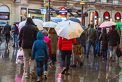 London, December 31 2017. The umbrellas come out as a downpour begins in London's west end ahead of the New Year's Eve fireworks at midnight. PICTURED: People make their way towards the underground at Piccadilly Circus. © SWNS