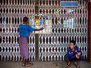 20 NOVEMBER 2017 - YANGON, MYANMAR: A security guard sits on the ground in front of the passenger exit at the Dala Ferry terminal. Tens of thousands of commuters ride the ferry every day. It brings workers into Yangon from Dala, a working class community across the river from Yangon. A bridge is being built across the river, downstream from the ferry to make it easier for commuters to get into the city.     PHOTO BY JACK KURTZ