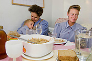 """Aug 10, 2008 -- COLORADO CITY: Members of the Jessop family at Sunday dinner in their home in Colorado City, AZ. The Jessops are polygamists and members of the FLDS. Colorado City and neighboring town of Hildale, UT, are home to the Fundamentalist Church of Jesus Christ of Latter Day Saints (FLDS) which split from the mainstream Church of Jesus Christ of Latter Day Saints (Mormons) after the Mormons banned plural marriage (polygamy) in 1890 so that Utah could gain statehood into the United States. The FLDS Prophet (leader), Warren Jeffs, has been convicted in Utah of """"rape as an accomplice"""" for arranging the marriage of teenage girl to her cousin and is currently on trial for similar, those less serious, charges in Arizona. After Texas child protection authorities raided the Yearning for Zion Ranch, (the FLDS compound in Eldorado, TX) many members of the FLDS community in Colorado City/Hildale fear either Arizona or Utah authorities could raid their homes in the same way. Older members of the community still remember the Short Creek Raid of 1953 when Arizona authorities using National Guard troops, raided the community, arresting the men and placing women and children in """"protective"""" custody. After two years in foster care, the women and children returned to their homes. After the raid, the FLDS Church eliminated any connection to the """"Short Creek raid"""" by renaming their town Colorado City in Arizona and Hildale in Utah.     Photo by Jack Kurtz / ZUMA Press"""